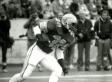 ISU football player 32 running with the ball at the Homecoming Game, 1985
