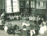 Children gathered around Christmas tree, The University of Iowa, 1920s