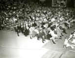 Alumni seated in folding chairs at the night before Homecoming Pep Rally, 1969