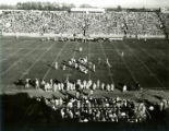Football players on the field during the Homecoming football game, 1959