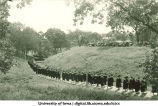 Commencement procession on west side of Iowa River, with Quadrangle Residence Hall on right, The University of Iowa, 1920s