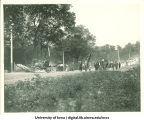 Students marching over bridge near City Park for Senior Frolic, The University of Iowa, 1910s