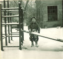 Small girl playing with snow on a slide, The University of Iowa, January 1938