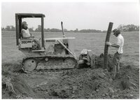 1979 - Man on Bulldozer in front of Man putting pipe in the ground
